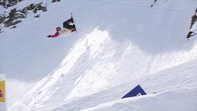 Snowboarder jump from springboard, make dangerous flips. Landscape of mountains.