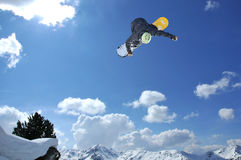 Snowboarder jumping. A freestyle snowboarder jumping with the alps in the background royalty free stock photos