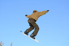 Snowboarder jumping. Photo of a young male snowboarder jumping against a blue sky Royalty Free Stock Image