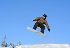Snowboarder jumping. Photo of a young male snowboarder jumping against a blue sky Royalty Free Stock Images