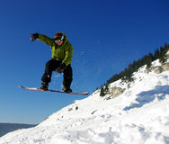 Snowboarder jumping. Over the blue sky Royalty Free Stock Image