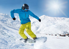 Snowboarder jumping. Active snowboarder jumping high in the mountains Stock Image