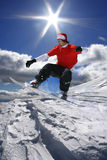 Snowboarder jumping against blue sky Royalty Free Stock Photo