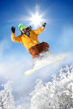 Snowboarder jumping against blue sky Stock Photos