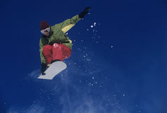Snowboarder Jumping Against Blue Sky. Low angle view of a male snowboarder jumping with snowboard against blue sky Royalty Free Stock Image
