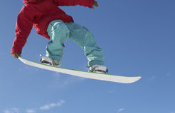 Snowboarder Jumping Against Blue Sky. Low section of male snowboarder jumping against blue sky Royalty Free Stock Image
