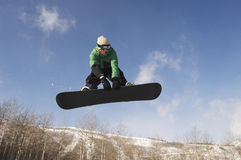 Snowboarder Jumping Against Sky. Low angle view of male snowboarder jumping against sky Royalty Free Stock Images