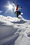 Snowboarder jumping against sun Stock Photography