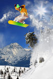 Snowboarder jumping against sun Stock Photos