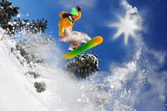 Snowboarder jumping against sun Stock Image
