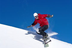 Snowboarder jumping through air with deep blue sky. In background Stock Image