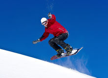 Snowboarder jumping through air with deep blue sky Stock Image