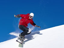 Snowboarder jumping through air with deep blue sky. In background Royalty Free Stock Photos