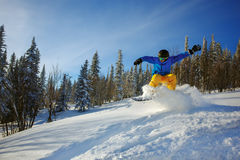 Snowboarder jumping through air with deep blue sky in background Royalty Free Stock Photos