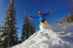Snowboarder jumping through air with deep blue sky in background Stock Photography