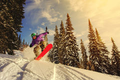 Snowboarder jumping through air with deep blue sky in background Royalty Free Stock Image