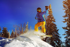 Snowboarder jumping through air with deep blue sky in background Royalty Free Stock Photo