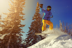 Snowboarder jumping through air with deep blue sky in background Stock Image