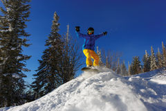 Snowboarder jumping through air with deep blue sky in background Royalty Free Stock Images