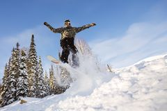 Snowboarder jumping from the springboard against the sky Stock Photos