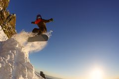 Snowboarder jumping through air with deep blue sky in background stock photos