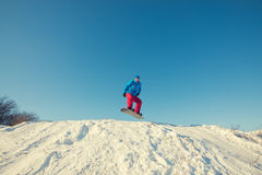 Snowboarder jumping on background of blue sky. Snowboarder jumping on the background of blue sky, in winter forest Stock Image
