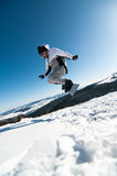 Snowboarder jumping on blue sky background Royalty Free Stock Image