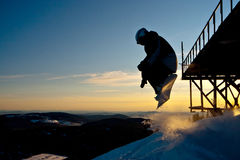 Snowboarder jumping from the bridge. Lady snowboarder freeride in Siberia Stock Photos