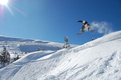 Snowboarding Jump. Snowboarder jumping from a cliff in snow powder. Ukraine, Carpathians, Dragobrat Stock Images