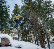 Snowboarder jumping in the forest. Snowboarder jumping over the snow-covered stone on the background forest. Low angle view Royalty Free Stock Photo
