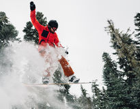 Snowboarder is jumping and freeriding in the mountain forest. Snowboarder with special equipment is jumping very high and freeriding from hill in the mountain Stock Image