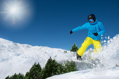 Snowboarder jumping high in the air. Winter vacation -  snowboarder jumping high in the air on a cold sunny day Stock Photo