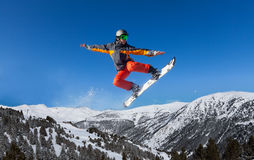 Snowboarder jumping high like ninja. Snowboarder jumping high in the air with the board like ninja Stock Image