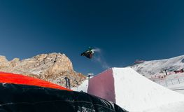 Snowboarder jumping on kicker, balloon landing, Val di Fassa Dolomiti snow park. Mountains on background Stock Photography