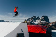 Snowboarder jumping on kicker, balloon landing, Val di Fassa Dolomiti snow park. Mountains on background Stock Images