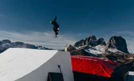 Snowboarder jumping on kicker, balloon landing, Val di Fassa Dolomiti snow park. Mountains on background Royalty Free Stock Photo