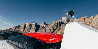 Snowboarder jumping on kicker, balloon landing, Val di Fassa Dolomiti snow park. Mountains on background Stock Photos