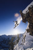 Snowboarder Jumping From Mountain Ledge. Low angle view of snowboarder jumping from mountain ledge Stock Photography