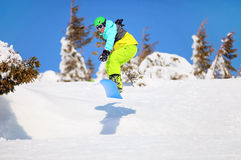 Snowboarder jumping on mountain slope Stock Photography