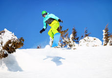 Snowboarder jumping on mountain slope. Young male snowboarder jumping on mountain slope Royalty Free Stock Images