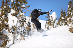 Snowboarder jumping on mountain slope. Young male snowboarder jumping on mountain slope Royalty Free Stock Photography