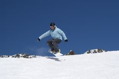 Snowboarder jumping in the mountains. Snowboarder jumping in the snowy mountains Stock Photos