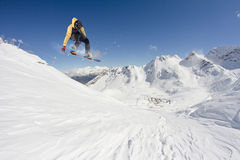 Snowboarder jumping on mountains. Extreme snowboard freeride sport. Stock Image