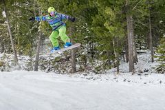 Snowboarder jumping in the mountains on a forest background royalty free stock image