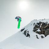 Snowboarder jumping in mountains. Jumping snowboarder in mountains on the snowboard Stock Images