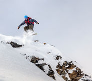 Snowboarder jumping in mountains. Jumping snowboarder in mountains on the snowboard Royalty Free Stock Photos