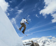 Snowboarder jumping in mountains. Jumping snowboarder in mountains on the snowboard on blue sky background Royalty Free Stock Images