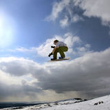 Snowboarder jumping in mountains. Jumping snowboarder in mountains on the snowboard on blue sky background Stock Photos