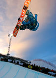 Snowboarder jumping. Pro snowboarder jumping from a half pipe during night session in Aspen, Colorado Stock Photo