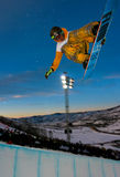 Snowboarder jumping. Pro snowboarder jumping from a half pipe during night session in Aspen, Colorado Stock Images